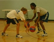 KU women's basketball player Sade Morris, right, jokes with camper Michaela Neuhus, 13, of Denver during a dribbling drill. Morris is a member of a six-player sophomore class.