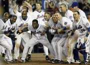 Members of the New York Mets wait for teammate Shawn Green to cross home plate after he hit the winning home run in the 11th inning. Green's homer lifted the Mets to a 2-1 victory Monday in New York.