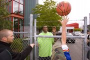 Fans throw a basketball over a fence to be autographed by NBA hopeful Kevin Durant, center. He toured the SuperSonics' facilities and met with team executives Sunday in Seattle.