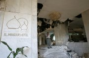 A man talks on his cell phone in the bombed-out lobby of the Mansour Hotel in Baghdad. A suicide bomber apparently targeting a meeting of U.S.-allied Sunni sheiks penetrated layers of security and blew himself up Monday in the lobby, killing four of the tribal leaders, police reported.