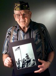 Charles W. Lindberg, one of the U.S. Marines who raised the first American flag over Iwo Jima during World War II, holds a photo of the event in this June 7, 1999, photograph in Grand Forks, N.D. He is standing behind the Marine holding a rifle. Lindberg died Sunday at age 86.