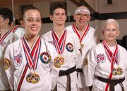 These students at the ATA Blackbelt and Leadership Academy in Lawrence were named world champions at a recent competition in Little Rock, Ark. They are, from left, Fe Brinkley, Dru Forrester, and Bill and Ginger Vermooten. Not pictured is Jimmy Golden, a 2007 sparring world champion.