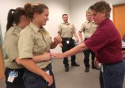 New Douglas County corrections officers, from front left, Megan Walker and Amber Davatz practice positioning for the Heimlich maneuver with sheriff's officer and instructor Deb Porter during training at the Douglas County Jail. In background at center are new corrections officers Dereck Martinez, left, and Brett Larve. The Douglas County Jail is experiencing its highest shortage of corrections officers in six years.