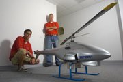 Kansas University alumnus Lance Holly, director of unmanned air vehicle projects at Viking Aerospace, left, and Bill Donovan, KU graduate student and director of UAV design, build and operate unmanned air vehicles like the helicopter shown above. They have hopes their 2-year-old company will soon expand and provide UAVs for companies and civil service agencies.