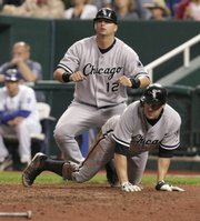 Chicago's A.J. Pierzynski (12) and Scott Podsednik look back to check the action after they scored what proved to be the game-winning runs. They crossed the plate thanks to a single by Tadahito Iguchi in the White Sox's 3-1 victory over the Royals on Saturday in Kansas City, Mo.