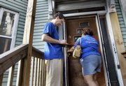Leaders from the Greater Boston Interfaith Organization, Steve Vogel, left, and Debbie Varrs, leave information about Massachusetts' new health care reform law at an unanswered door during their informative outreach campaign Thursday in Boston's Roxbury section. The state's landmark health insurance law reaches a critical marker on Sunday - the official date that nearly everyone in Massachusetts must be insured or face a series of increasing tax penalties.