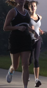 Participating in an early-morning run in the EZ8 camp for women are Erin Parmelee, left and Rachel Combs. The EZ8 is an eight-week, outdoor running camp designed to help women of all fitness levels achieve their running goals. The group meets Monday, Wednesday and Friday mornings at sites throughout Lawrence.