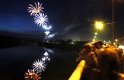 A stream of fireworks are reflected from the Kansas River as observers line the Kansas River Bridge Wednesday night for the show.