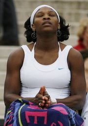 Serena Williams contemplates her dropping out at Wimbledon on Wednesday. Williams was defeated by Justine Henin, 6-4, 3-6, 6-3, on the Centre Court in England.