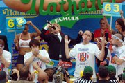 Joey Chestnut, second from right, of San Jose, Calif., throws his hands up at the end of Nathan's Famous July Fourth International Hot Dog Eating Contest in Brooklyn, N.Y. Chestnut beat Japan's Takeru Kobayashi, left, the six-time defending champion.