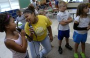 "Sophia Walters, 8, left, and group leader Mercades Beckum sing karaoke to Whitney Houston&squot;s ""I Wanna Dance with Somebody"" as they play the video game SingStar on Friday morning during the Boys and Girls Club Summer Camp at Cordley School."