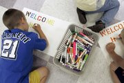 Several young boys work on welcome home signs for their fathers June 27 at Camp Noah in Baxter, Minn. The camp is a free program for children with parents serving in the National Guard and offers an opportunity for them to share their cares.