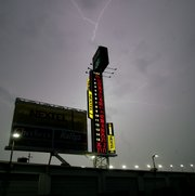 Lightning dances across the sky over the Nextel scoring tower at the Daytona International Speedway. Rain Friday forced cancellation of qualifying for tonight's Nextel Cup race and postponed the Busch Series race until this morning.