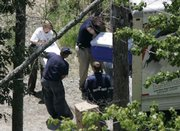State and federal officials load coolers of evidence into a truck as they search the grounds behind a home owned by Atlanta Falcons quarterback Michael Vick. The officials were looking for evidence in a possible dog fighting investigation Friday in Smithfield, Va.