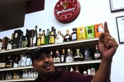 John Augusto, who works at Alvin's Wine & Spirits, 905 Iowa, tells stories Thursday night about different situations that occur while working at a liquor store. Alvin's has a security policy that at least two employees must be in the store at all times.
