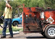 "A warning sign on the truck reads ""hot"" as Stan Hofer from Blacktop Inc. wipes his brow as he works on sealing cracks at the St. Stephen&squot;s parking lot with his cousin, David Hofer, Friday in Billings, Mont. Billings broke a record Friday as temperatures hit 104 degrees."