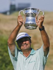 Brad Bryant holds up the championship trophy on the 18th hole after winning the U.S. Senior Open.