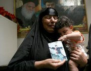Umm Nasser holds a photograph of her grandson, Muntader Nasser, 13,  who was arrested Friday with his two brothers and his father, senior Shiite cleric Sheik Nasser al-Saidi, in a raid by U.S. and Iraqi soldiers. Nearly 1,000 Shiites loyal to anti-American cleric Muqtada al-Sadr took to the streets Monday in the Shu'la neighborhood of Baghdad, demanding the release of Sheik Nasser al-Saidi and other detainees.