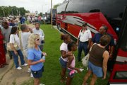 Coffeyville residents displaced by the recent flood await their turn to board buses for a tour of the restricted area Monday.
