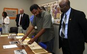 Kevin Willmott, Kansas University associate professor of theatre and film, center, and Associate Vice Provost Maurice Bryan, right, look through items displayed from the African-American Collection on Wednesday morning during a meeting of the Kansas African American Affairs Commission at the Spencer Research Library.