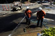Francisco Mondradon, left, and Juan Cabrera of LRM Industries clear off the corner of 10th and Massachusetts streets on Friday after a final layer of asphalt was laid.