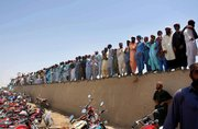 "Mourners stand over a wall during the funeral ceremony of pro-Taliban Pakistani cleric Abdul Rashid Ghazi, who was killed in the siege of the Red Mosque, Thursday at his ancestral village Basti Abdullah, Pakistan. The captured chief cleric of the Red Mosque led prayers for his slain brother, and forecast that the death of the mosque&squot;s defenders would push Pakistan toward an ""Islamic revolution."""