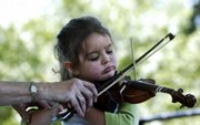 Violin instructor Julie Holmberg helps 3-year-old Vivian Podrebarac play Friday during a violin recital at South Park.