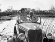 "A December 1959 photo shows then-Sen. Lyndon B. Johnson and Lady Bird Johnson crossing the Pedernales River in their 1934 ""Deluxe Phaeton"" convertible."