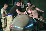"U.S. airmen from the 332nd Expeditionary Aircraft Maintenance Squadron repair a F-16 Falcon on June 21 at Balad Air Base, 50 miles north of Baghdad. The Air Force has been quietly building its Iraq presence during the ""surge"" in U.S. ground troops."