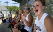 Tonganoxie Braves players Lindsey Fatherley, right, and Ashlee Lohman laugh it up on the bench as they watch spectators dodge a foul ball during the AFA Nationals against the Ottawa Sabotage Wednesday at the Clinton Lake Softball Complex. The Braves defeated the Sabotage 2-0 in extra innings.