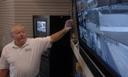 Jack Proctor, sales manager at Rueschoff Security Systems, talks about the types and qualities of various security camera systems and monitoring equipment. Proctor was viewing a monitor display of nine security cameras at Rueschoff's offices Wednesday. .
