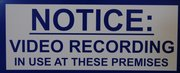 A sign informs people that they may be recorded if they enter a property.