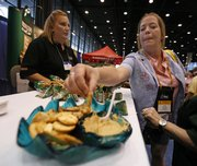 Robin Lightfoot, of Garden City, Kan., listens to Kathy Cheop as she samples hummus at the Wild Garden booth at the School Nutrition Association annual meeting this week in Chicago. The push for healthy options has food companies scurrying to find creative, healthy alternatives like single-serve portions of hummus that could become kid-friendly favorites.