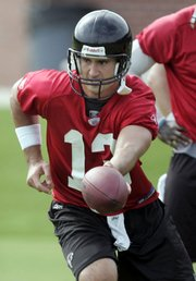 Atlanta quarterback Joey Harrington hands off during a minicamp. Harrington enters training camp as the Falcons' starter with superstar Michael Vick facing federal charges.