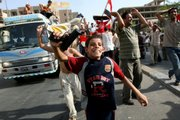 An Iraqi boy waves a toy pistol in central Baghdad after the country's national soccer team beat South Korea in the Asian Cup to reach the tournament's final. The celebrations Wednesday later turned to sorrow as a pair of suicide bombers targeted the fans, killing at least 50.