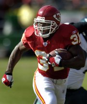 Kansas City running back Priest Holmes runs against the Philadelphia Eagles in October 2005, the last month he suited up for the Chiefs. The team announced Wednesday that Holmes would report to training camp Saturday in River Falls, Wis.
