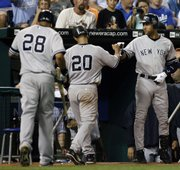 New York's Jorge Posada (20) is congratulated by Derek Jeter, right, after Posada scored on a sacrifice fly by Melky Cabrera (28) in the seventh inning. The Yankees beat the Royals, 7-1, Wednesday in Kansas City, Mo.
