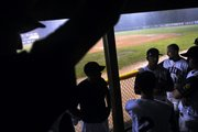 The Lawrence Raiders listen to coach Shaun Edmondson in the dugout after learning their American Legion Zone Tournament game was postponed to today because of rain.  The  Raiders led, 2-0, when the game was called.