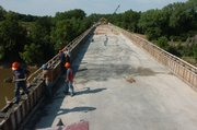 Workers for A.M. Cohron & Son Inc. work on schedule to get the bridge over the Kansas River complete by Aug. 10. Crews baked under the sun on Friday.