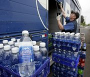 PepsiCo deliveryman Nick Jones unloads Aquafina water and other Pepsi products while making a 2006 delivery in Tualatin, Ore. The label on Aquafina water bottles will soon reflect that the drink comes from the same source as tap water.