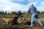 Salina area Chamber of Commerce president and CEO Dennis Lauver, left, and senior vice president Don Weisman shovel Rhinoceros manure.