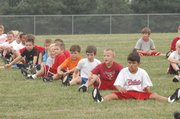 Members of the Lawrence youth football gorillas perform stretching exercises before the first practice of the season. More than 60 players gathered Tuesday at Sunflower Elementary School.