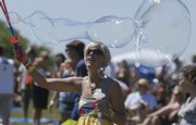 Amy Roller, of Des Moines, Iowa, releases a stream of bubbles on the lawn at the Revival Stage during the Wakarusa Music & Camping Festival in June. Bubbles last longer in humid conditions, something Kansas is rarely short on this time of year.