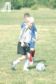 Eight-year-old Eric Groefke dribbles the ball during the KVSA's preseason soccer camp Monday at Youth Sports Inc.