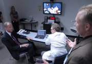 Congressman Jerry Moran, R-Kan., left, listens to Ryan Spaulding, director of Telemedicine for Kansas University Medical Center, right, as Dr. Gary Doolittle, center, talks to a patient at Hays Medical Center using the tele-technology.