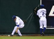 Kansas City's David DeJesus, left, fields a double as Joey Gathright collides with the wall. Two runs scored on the play, and that proved to be enough in Toronto's 2-1 victory against the Royals on Friday in Kansas City, Mo.