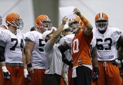 Cleveland quarterback Brady Quinn, right, goes over a play with teammates during training camp. Quinn will not  start tonight's game against Kansas City but could move up the depth chart if Charlie Frye or Derek Anderson struggle.