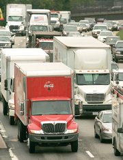 Trucks and cars appear together in slow moving traffic Friday on Interstate Route 93 in Newton, Mass. In the decade from 1995 to 2005, the weight load on urban highways increased 54 percent.
