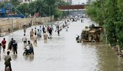People walk through a flooded street Friday in Karachi, Pakistan. Heavy rains lashed Pakistan's largest city, collapsing houses, flooding streets and leaving at least 22 people dead, an official said.