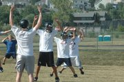 Members of southwest junior high's eighth-grade football team do calisthenics during the first day of practice Monday at Southwest Junior High.